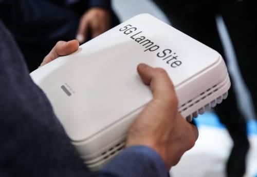 在德国汉诺威工博会上,一名参观者手持华为展区展出的一个5G小基站。新华社