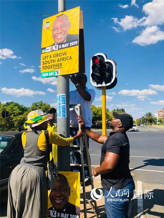 竞选人员悬挂竞选海报。(图片来源:人民网)