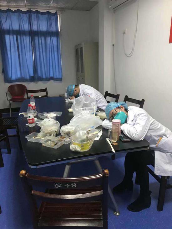 感染科二病区交接后在桌上趴着睡着的医护人员。