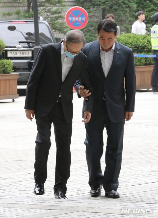 3日下午,李明博被搀扶着走向法庭。(纽西斯通讯社)