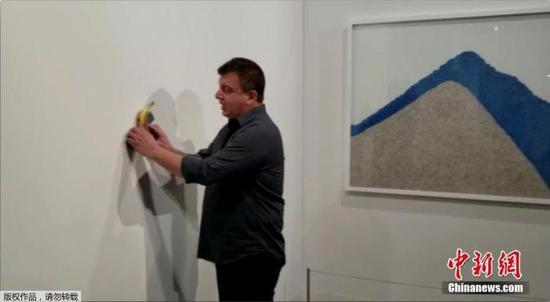 当地时间12月7日,美国迈阿密海滩,意大利艺术家毛里·卡特兰标价12万美元的作品《喜剧演员》在巴塞尔艺术展上展出时,被行为艺术家达图那当场吃掉。