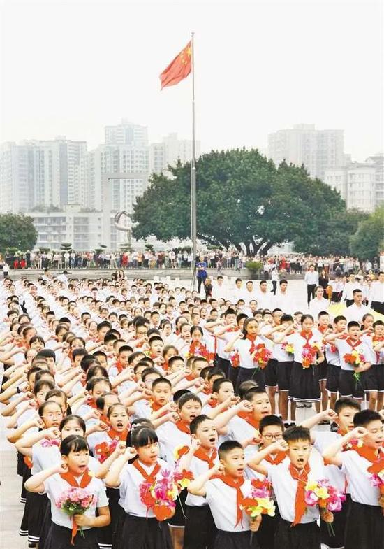 """重庆市沙坪坝区红岩魂广场上,1000余名师生齐聚于此,参加升国旗仪式、聆听国旗的故事,并一同进行宣誓。""""开学第一课"""",从升国旗开始。图片来源:重庆日报"""