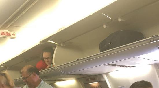 空姐趴在行李架上。(图源:推特)