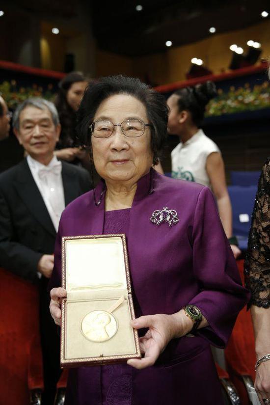 在瑞典首都斯德哥尔摩音乐厅举行的2015年诺贝尔奖颁奖仪式结束后,中国科学家屠呦呦展示获得的奖章(新华社)