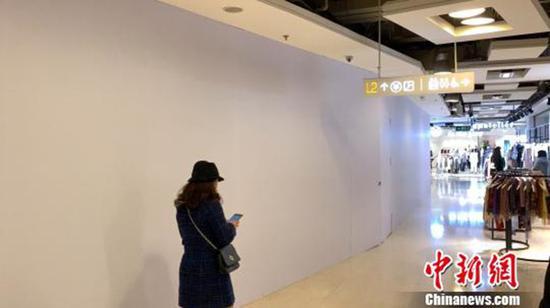 涉事店铺已闭店并用白色木质板材阻隔在表围进走了封闭式遮盖