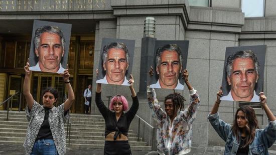 ▲抗议者举着印有杰弗瑞·爱泼斯坦肖像的标语在纽约联邦法院外示威