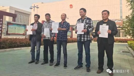 4月11日下午,周继坤等5人拿着无罪的判决书在安徽省高院前合影。