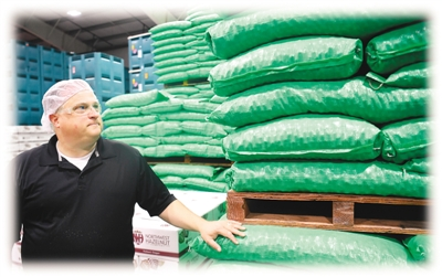 图为在美国俄勒冈州波特兰市南部威拉米特河谷一个榛子加工企业,总裁拉里·乔治站在尚未能售出的榛子产品旁。这些产品计划销往中国。新华社记者 吴晓凌摄