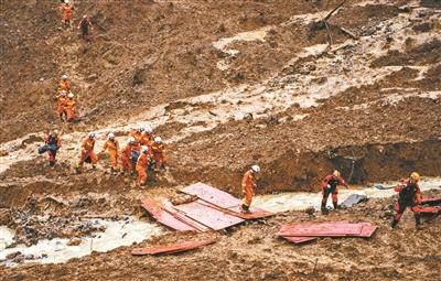 救济 职员在山体滑坡现场发展救济 供图/新华社