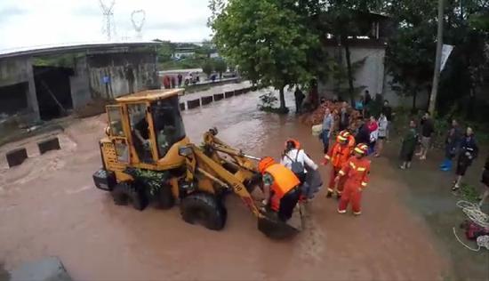 9月13日,四川仁壽一州里有衡宇被淹,救火員經由過程推土機將被困職員救出。眉山消防供圖