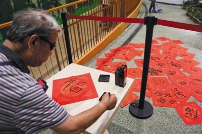 参不益望中国馆的游客体验写福字。