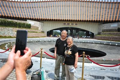 来参不益望的游客在中国馆外拍照留念。