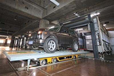 停车机器人载着托盘和上面的汽车自动驶入车库停车位。