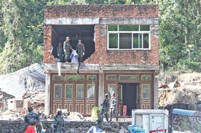 8月12日,温州永嘉山早村,武警在受灾损坏的房屋内进行清理。本版摄影/新京报记者 王嘉宁