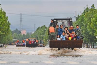 昨日14时36分,山东章丘相公庄,铲车行驶在洪水中转移被困群众。