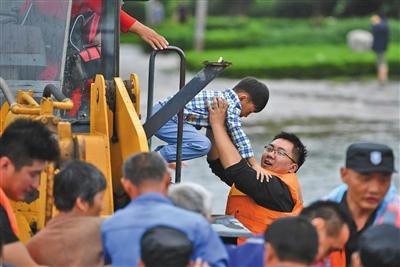 昨日15时整,这位小男孩被安排在铲车驾驶室里转移,一位志愿者把他接下铲车。