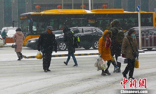 市民顶着雪前走。 王幼军 摄