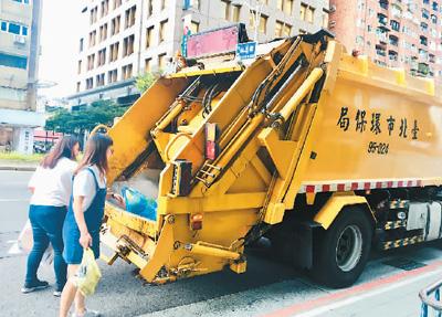 台湾民众将垃圾投入垃圾车内。柴逸扉摄