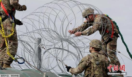 资料图:当地时间2018年11月2日,美国得州Hidalgo,中美洲移民大军压境美国,美国士兵在美墨边境安装铁丝网严防移民入境。