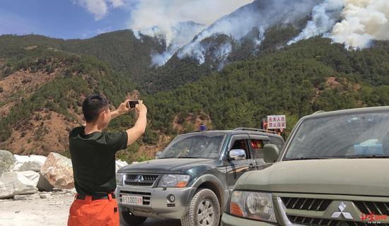 冕宁县森林大火扑火现场,消防队员在拍摄森林大火画面