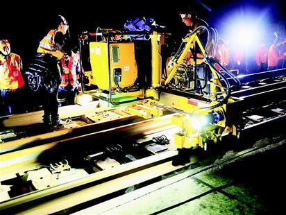 图为:换轨机将旧钢轨移至道床外。(张俊 摄)