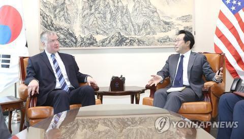 原料图:李度勋(右)与比根(韩联社)