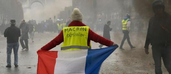 """示威者身穿写有""""马克龙下台""""口号的背心 图自法新社"""