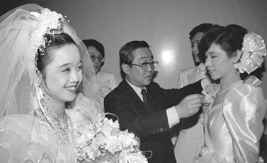1988年2月6日,特地从事婚礼照相的中日合资照相馆总经理高崎纪一郎(中)在北京民族文化宫为参与集体婚礼的新娘整理服装。