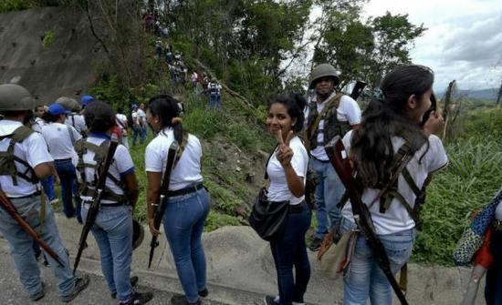 原料图:委内瑞拉女民兵身着白色T恤牛仔裤身背枪参添操练。