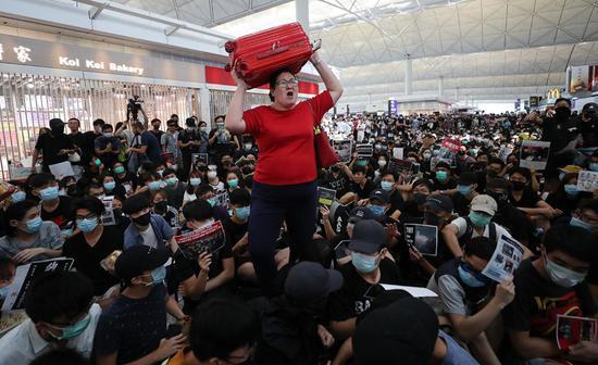 图为红衣女子举着行李箱越过示威者的照片(来源:法新社)