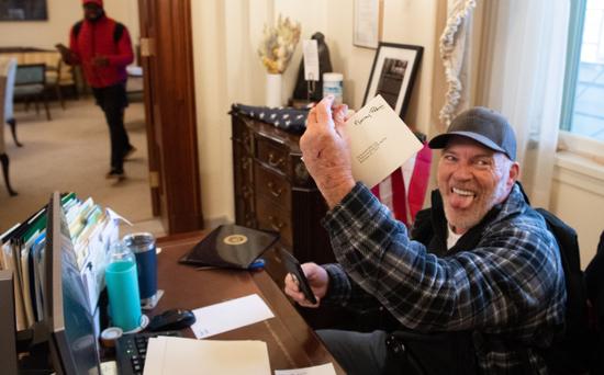 把脚跷在佩洛西办公桌上并拿走一封信的男子也被逮捕。
