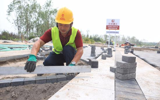 7月15日,北京市朝阳区温榆河公园施工现场,工人正在为步道铺设海绵砖。新京报记者 王嘉宁 摄