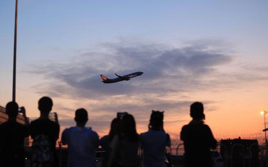 爱好者拍摄飞离的航班。(图源新京报)