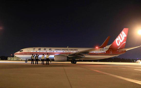工作人员向最后一班离港航班挥手告别。(图源新京报)