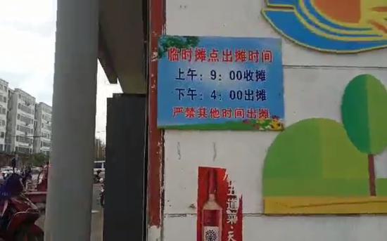 """在事发地东侧的一面文化宣传墙上,挂有一处临时摊点的牌子,其上注明""""上午收摊时间为9点,下午出摊时间为4点""""。 受访者供图"""