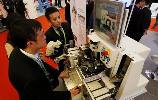 原料图:2017年3月14日,一位做事人员(左)在向参不都雅者演示一台半导体焊线机的操作。当日,2017中国国际半导体设备与原料展览暨钻研会在上海开幕。(新华社)