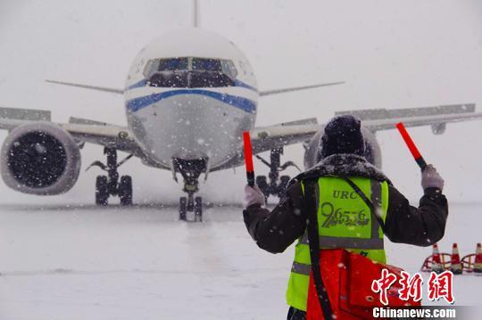 4日,乌鲁木齐国际机场迎来降雪。 郭一彤 摄