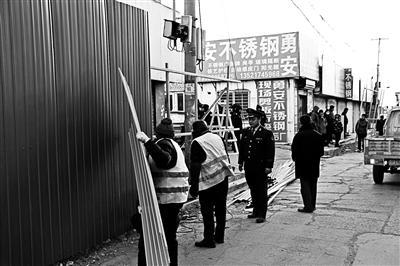 """12月15日,北京昌平消防聯合屬地街道對水屯市場西側""""水泥一條街""""存在安全隱患的門臉房及住宿房進行了查封并對被查封的門臉房進行了""""硬化隔離""""。 北京青年報 圖"""