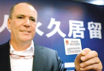 ▲一名外籍人士在首发仪式上展示刚领取的《中华人民共和国外国人永久居留身份证》。