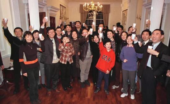 1999年12月20日零时,在中国驻英国大使馆教育处收看澳门回归祖国电视现场直播的留英学子举杯欢庆。新华社记者 庞伟良 摄