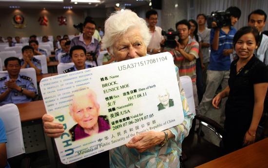 """▲一名获得中国永久居留证的美国人展示自己的""""绿卡""""。"""