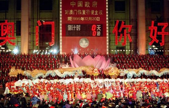 """""""北京市人民迎接澳门回归祖国联欢晚会""""在天安门广场澳门回归倒计时牌前举行。图为倒计时牌显示0秒时,广场上人群欢动。左右两侧大字为""""澳门,你好。""""罗更前 摄"""