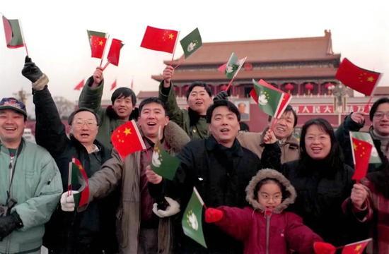 1999年12月20日,澳门回归祖国第一天,北京市民纷纷来到天安门广场庆祝澳门回归。图为北京金洋房产开发有限公司职工挥舞着国旗、澳门特别行政区区旗在天安门前留影。新华社记者 王呈选 摄