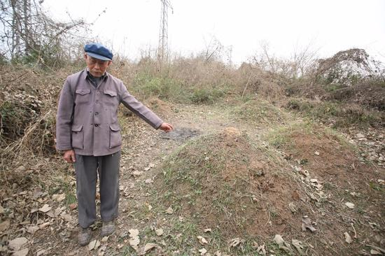 ▲幸存者梅寿芳的10位亲人被日军杀害。图为他指认埋葬10位亲人的墓地 。