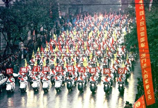 """1999年12月20日,重庆市举行千乘""""回归彩车""""巡游活动,喜庆澳门回归祖国。图为由千辆重庆市自产的汽车、摩托车组成的方阵在市区街道巡游。新华社记者 杨磊 摄"""