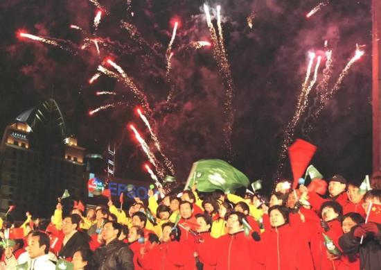 1999年12月19日晚,上海市各界人士汇聚黄浦江畔举行盛大的庆澳门回归联欢晚会。图为12月20日零点以后,礼花腾空,兴奋的人群热烈欢呼。新华社记者 凡军 摄