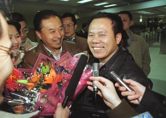 1999年12月20日零时,中国政府对澳门恢复行使主权的第一天,广东珠海拱北海关迎来了第一位澳门同胞,黄灼培(右一)。新华社记者 壮锦 摄