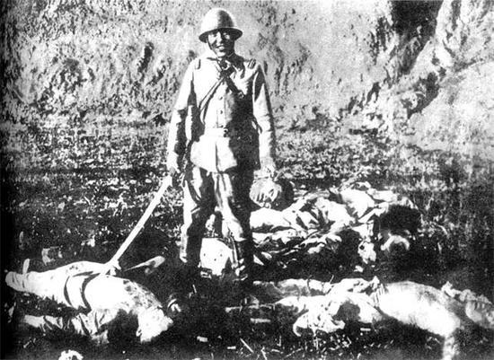 ▲一名日军官兵在砍杀数名中国人后,提起一颗血淋淋的人头,让人为其拍照留念。选自《罪证:日军镜头中的侵华记录》