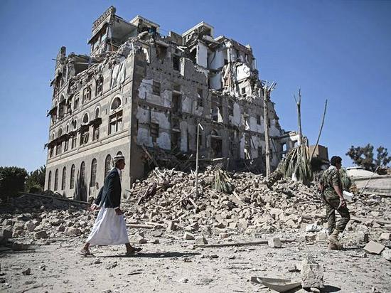 12月6日,也门首都萨那,胡塞武装人员从一栋在空袭中被炸毁的建筑旁走过。(新华/美联)