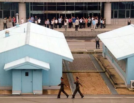 ▲资料图片:来自世界各国的游客在板门店韩国一侧(上)参观,画面下部为朝鲜一侧,两名朝鲜人民军士兵正在执勤。